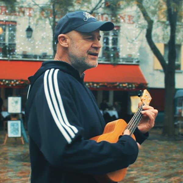 man playing small guitar